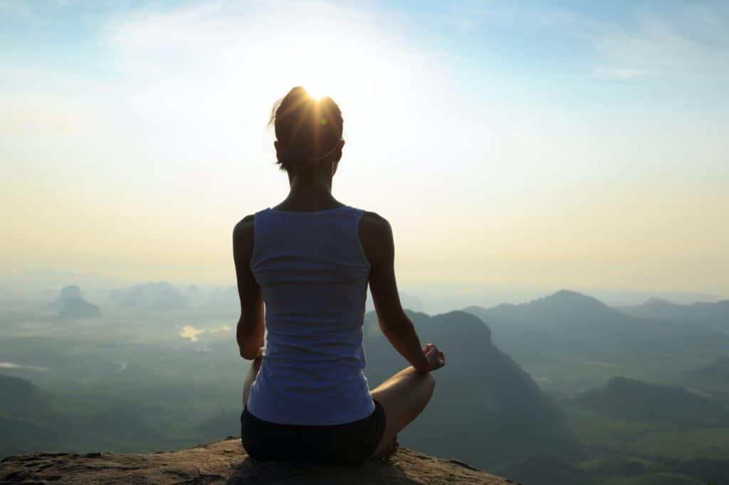 Meditazione sul bordo della scogliera in cima alla montagna all'alba