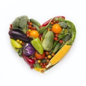 Cornice a forma di cuore di verdure fresche su sfondo bianco